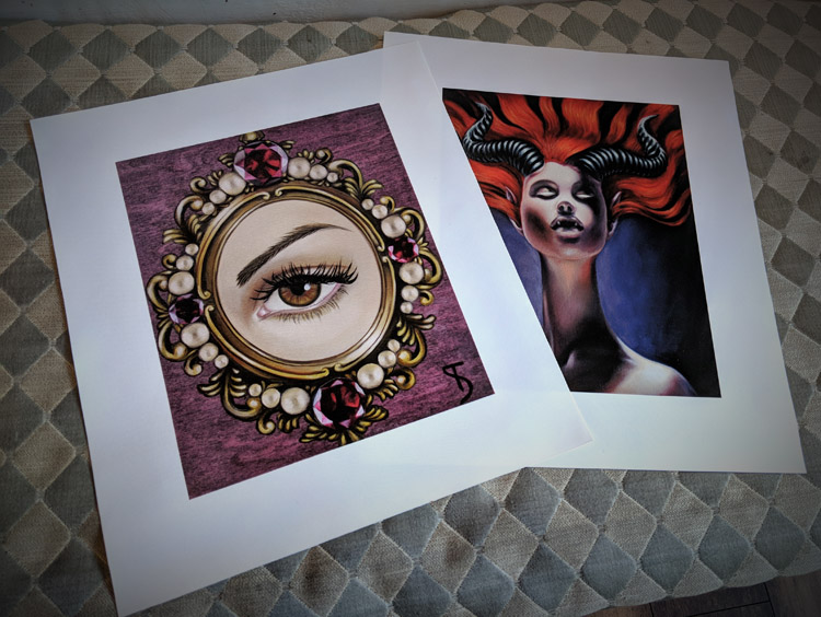 "Art Prints from left to right ""Lover's Eye Hazel"" and ""Horny Beast"""